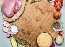 Ingredients for cooking a turkey breast couscous cucumber radish tomato onion seasoning herbs. on wooden rustic background close u Stock Photography
