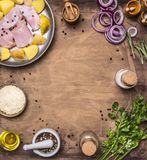 Ingredients for cooking turkey breast with pear, rice, herbs, and vegetables are laid out on a round cutting board Stock Photos