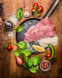 Ingredients for cooking turkey steak with rice seasoning vegetables in a frying pan on a wooden rustic background top view Stock Image