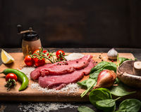 Ingredients for cooking turkey steak on a wooden cutting board on a dark wooden background close up Royalty Free Stock Photos