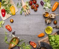 Ingredients for cooking vegetarian food cherry tomatoes, bell peppers, arugula different kinds of salad, seasoning, wooden spoon royalty free stock photography