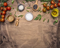Ingredients for cooking vegetarian food  cherry tomatoes, spices, herbs, oil, colorful rice in wooden spoons border ,place for tex Royalty Free Stock Image