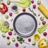 Ingredients for cooking vegetarian food, corn, radishes, rosemary, pepper, oil, seasonings, lined around pan place for text,fr stock images