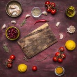 Ingredients for cooking vegetarian food tomatoes on a branch, lemon, olive oil, red hot pepper, herbs, cutting board , frame, with Stock Photography