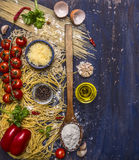 Ingredients for cooking vegetarian pasta with cheese, oil, vintage wooden spoon, pepper cherry tomatoes on a branch on wooden Stock Photography