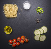 Ingredients for cooking vegetarian pasta with courgettes, cherry tomatoes, peas and pepper, laid  rustic chalkboard, place for Royalty Free Stock Photography