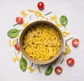 Ingredients for cooking vegetarian pasta with cherry tomatoes and herbs in a vintage pot on white wooden rustic background Royalty Free Stock Image