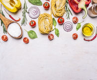 Ingredients for cooking vegetarian pasta with tomatoes, basil, oil, pepper on wooden rustic background top view border ,place Royalty Free Stock Photo