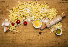 Ingredients for cooking vegetarian pasta with tomatoes, butter, eggs, rolling pin wooden rustic background top view close up Royalty Free Stock Photo