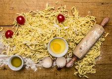 Ingredients for cooking vegetarian pasta tomatoes, butter, eggs, rolling pin on wooden rustic background top view close up Royalty Free Stock Photography