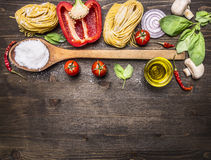 Ingredients for cooking vegetarian pasta with vegetables, a wooden spoon, herbs and butter on wooden rustic background top view cl Royalty Free Stock Photography