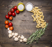 Ingredients for cooking vegetarian raw fusilli pasta with sunflower oil cherry tomatoes, mushrooms, rosemary place for text,frame Royalty Free Stock Photography