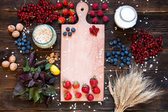 Ingredients for cooking veggie healthy breakfast. Strawberries, blueberries, nuts, oat, raspberries, red currants, mulberry, milk, basil. Top view, dark wooden Stock Photo