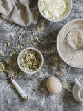 Ingredients for cooking whole grain multi seed bread - whole wheat flour, eggs, ricotta cheese, seeds, on a grey stone background. Stock Photos