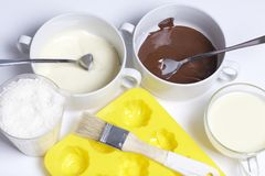 Ingredients for dessert are on the table. Cooking sweets with coconut and condensed milk. In a glaze of white and black chocolate.  stock image