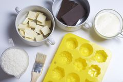 Ingredients for dessert are on the table. Cooking sweets with coconut and condensed milk. In a glaze of white and black chocolate.  royalty free stock photography