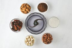 Ingredients for energy bites: nuts, dates, cocoa powder and coconut flakes with food processor on white table. Ingredients for energy bites: nuts, dates, cocoa royalty free stock photo