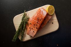 Ingredients, european and asian cuisine. Fresh salmon steak surrounded by lemon, spices and herbs on a wooden board. royalty free stock image