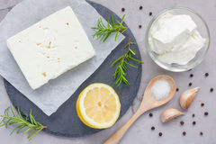 Ingredients for feta, cream cheese, rosemary, lemon and garlic dip on board, top view. Ingredients for feta, cream cheese, rosemary, lemon and garlic dip on stock images