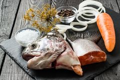 Ingredients for fish broth from salmon. Ingredients for fish broth: head and tail of salmon, onion, pepper, carrots, salt, bay leaf, dill umbrella. Dietary and Stock Images
