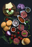 Ingredients For Cooking Burgers. Raw Ground Beef Meat Cutlets, Buns, Red Onion, Cherry Tomatoes, Greens, Pickles, Tomato Royalty Free Stock Photo