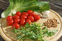 Ingredients for fresh vegetable salad on chopping board. Ingredients for fresh vegetable salad, tomatoes, arugla, romain lettuce, pine nuts, carlic, on wooden Stock Photography