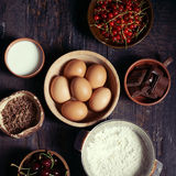 Ingredients for fruit and chocolate cake in rustic kitchen; sele. Ingredients for fruit and chocolate cake in rustic kitchen. Eggs, flour, chocolate, milk Stock Photos