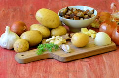 Ingredients for garlic soup on chopping board - potatoes, onion, garlic, roasted bread, parsley Royalty Free Stock Images