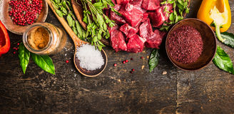 Ingredients for goulash or stew cooking: raw meat, herbs,spices,vegetables and spoon of salt on rustic wooden background, top view. Banner for website