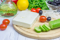 Ingredients for greek salad. On the cutting board and wooden table Stock Image