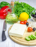 Ingredients for greek salad. On the cutting board and wooden table Royalty Free Stock Photography