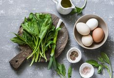 Ingredients for green shakshuka - fresh spinach, garlic, ramson and organic farm eggs on grey background. Top view Royalty Free Stock Photo