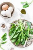 Ingredients for green shakshuka - fresh spinach, garlic, ramson and organic farm eggs on white background, top view. Healthy  food. Ingredients Stock Images