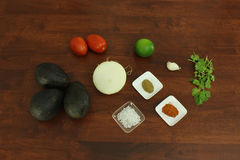 Ingredients for Guacamole. Food ingredients for guacamole recipe on a dark wood table top - avocado, plum tomato, onion, lime, clove of garlic, cilantro, cumin royalty free stock photography