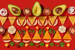 Creative geometric food pattern from mexican nachos corn chips, fresh vegetables, fruits, greens, chili, garlic - stock image