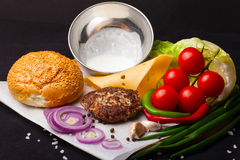 Ingredients for hamburger on a dark background. Royalty Free Stock Photography