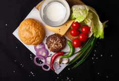 Ingredients for hamburger on a dark background. Top view. Royalty Free Stock Photography