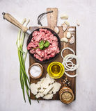 Ingredients for hamburgers, minced meat in a frying pan with pepper and onion rings  cutting board on wooden rustic background Royalty Free Stock Image