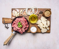 Ingredients for hamburgers, minced meat in a frying pan with pepper and onion rings  cutting board on wooden rustic background Royalty Free Stock Photo