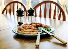 Freshly prepared traditional meal of Fish and Chips seen on a kitchen table. royalty free stock photo
