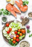 Ingredients for healthy, balanced lunch - salmon and vegetables. Red fish, zucchini, squash, cherry tomatoes, leek, wild rice, sp royalty free stock photos