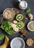 Ingredients for a healthy breakfast - chia pudding, oatmeal, banana, kiwi, spinach, coconut milk on a dark background, top view. royalty free stock photos