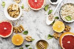 Ingredients of healthy breakfast food: oat flakes, kinoa, walnuts, floral honey, greens, oranges, bloody grapefruits on Stock Image