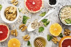 Ingredients of healthy breakfast food: oat flakes, kinoa, walnuts, floral honey, greens, oranges, bloody grapefruits on Stock Photography