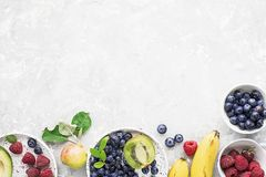 Ingredients of healthy breakfast: granola, cereal, nuts, berries, fruits, avocados, raspberries, blueberries, honey comb. Pears apples kiwi banana full of royalty free stock photos
