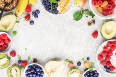Ingredients of healthy breakfast: granola, cereal, nuts, berries, fruits, avocados, raspberries, blueberries, honey comb. Pears apples kiwi banana full of royalty free stock photography