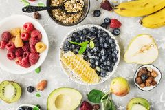 Ingredients of healthy breakfast: granola, cereal, nuts, berries, fruits, avocados, raspberries, blueberries, honey comb. Pears apples kiwi banana full of stock images