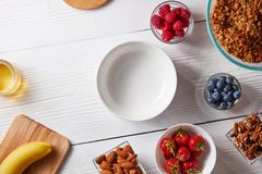 Healthy breakfast ingredients. Bowl of oat granola with fresh berries and nuts. Top view, copy space. Ingredients for a healthy breakfast - granola, nuts Stock Photography