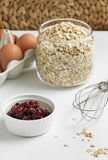 Ingredients for a healthy breakfast. Oatmeal porridge in the pot, eggs and cherry jam Royalty Free Stock Photo