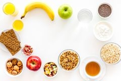 Ingredients for healthy breakfast. Fruits, oatmeal, yogurt, nuts, crispbreads, chia on white background top view copy Royalty Free Stock Photos